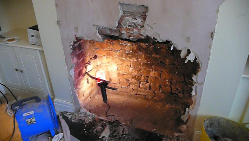 Opening up a fireplace for the installation of a wood burning ...