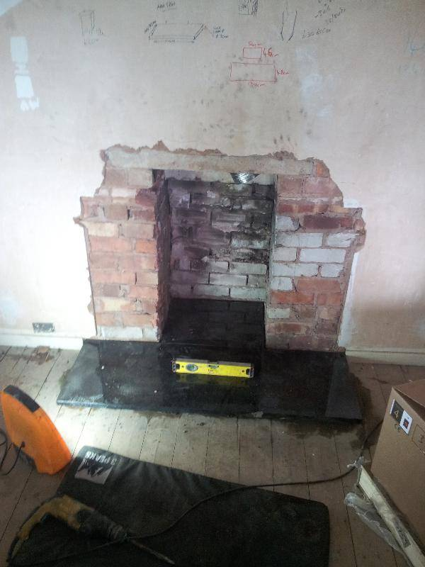 Opening up a fireplace for the installation of a wood ...