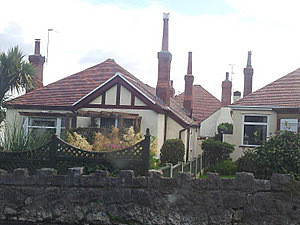 A regular housing estate with red tiled roof and long chimney stack